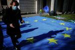 Мужчина в медицинской маске и ребенок с флагом на фоне разложенного на земле флага Европейского союза. Архивное фото