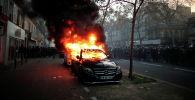 Автомобиль горит во время демонстрации против законопроекта О глобальной безопасности в Париже, Франция. 28 ноября 2020 года