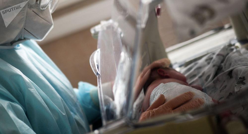 Врач осматривает ребенка в родильном отделении больницы. Архивное фото