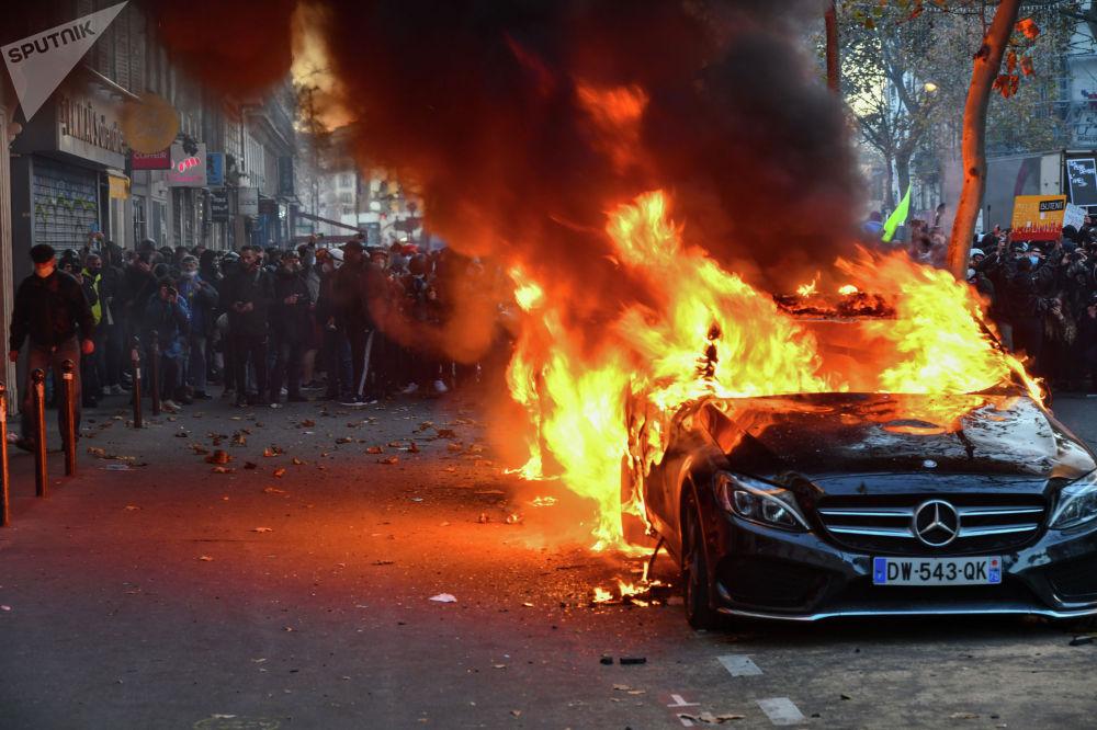 Парижде өрттөнгөн жеңил автоунаа жана митингге чыккан демонстранттар. Көчөгө чыккандар укук коргоо кызматкерлеринин мигранттарга кылган мамилесине жана Улуттук коопсуздук жөнүндө мыйзамына киргизилген өзгөртүүлөргө каршы пикирин билдирген