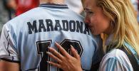 Диего Марадонанын жазуусу бар футболкачан киши. Архив