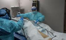 Медицинский персонал закрывает мешок с телом умершего пациента в отделении интенсивной терапии COVID-19 в Хьюстоне, штат Техас (США). 29 ноября 2020 года