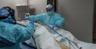 Медицинский персонал закрывает мешок с телом умершего пациента от COVID-19. Архивное фото