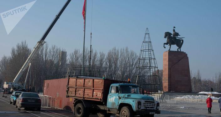 Сотрудники мэрии устанавливают новогоднюю елку на площади Ала-Тоо в Бишкеке
