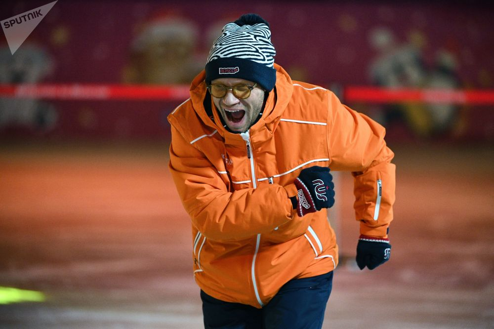 Вечерний Ургант шоусунун катышуучусу Дмитрий Хрусталев ырахаттануу менен муз тээп бара жатат