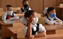 Школьники в защитных масках на уроке. Архивное фото