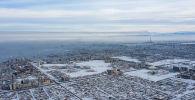 Вид с высоты на дома на территории Ленинского района Бишкека во время зимний холодов.
