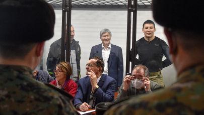 Бывший президент Кыргызстана Алмазбек Атамбаев улыбается, стоя за решеткой во время судебного заседания в Бишкеке 27 ноября 2020 года.