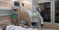 Медицинский работник у койки пациента в отделении реанимации. Архивное фото