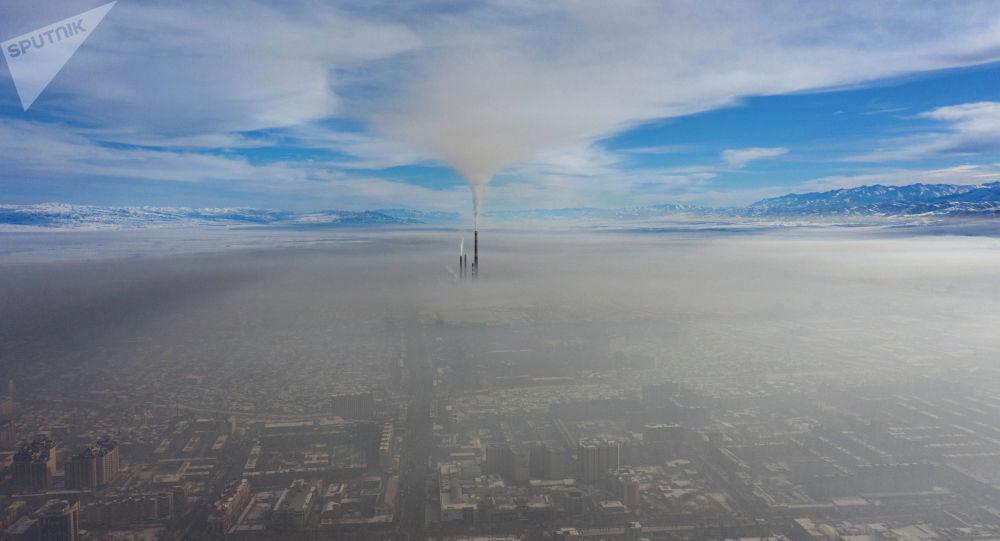 Вид на центр Бишкека и трубы ТЭЦ с высоты окутанные густым смогом