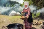 Женщина в национальной кыргызской одежде готовит боорсоки. Архивное фото