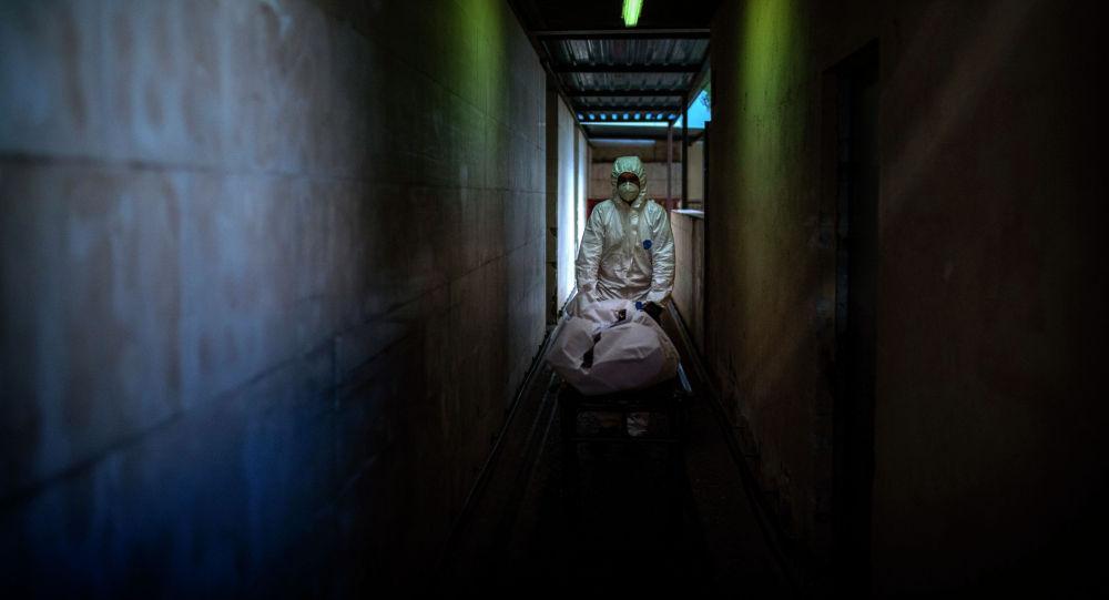 Работник морга переносит тело жертвы COVID-19. Архивное фото