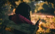 Девочка сидит на скамейке со смартфоном в руке. Иллюстративное фото
