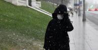 Женщина в защитной маске идет по улице. Архивное фото