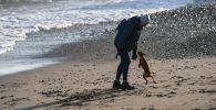 Женщина гуляет с собакой по набережной. Архивное фото