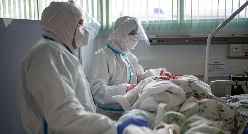 Медицинские работники и пациент в госпитале для больных COVID-19. Архивное фото