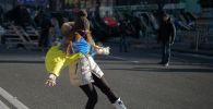 Девушка играет с мячом на улице Крещатик в Киеве.