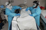 Медицинский персонал застегивает мешок для тела, в котором находится умерший пациент от COVID-19. Архивное фото