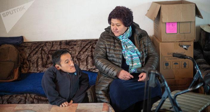 Кыргызстанка Айгуль Такырбашева с приемным сыном Уланом в своем доме