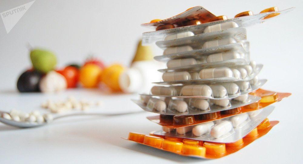 Упаковки витаминов в капсулах на фоне фруктов. Архивное фото