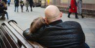 Пара обнимается на скамейке на улице города. Архивное фото