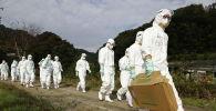Люди в защитных костюмах направляются на птицефабрику с подозрением на птичий грипп в Хигасикагаве, западная Япония