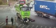 Два человека на скутере угодили под колеса самосвала, но чудом выжили благодаря шлемам. Случай зафиксировала камера наблюдения.