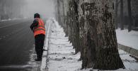 Сотрудник МП Тазалык чистит снег вдоль дороги в Бишкеке. Архивное фото