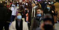 Люди в защитных масках идут по торговой улице в Риме, Италия. 15 декабря 2020 года