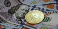 Сувенирная монета с логотипом криптовалюты биткоин и доллары США. Архивное фото
