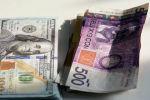 Пачка долларовых и сомовых купюр на столе. Иллюстративное фото
