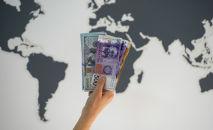 Девушка держит пачку долларовых и сомовых купюр на фоне карты мира. Иллюстративное фото