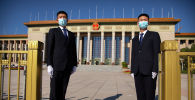 Бет капчан коопсуздук кызматкерлери Пекиндеги Чоң жыйындар залынын алдында күзөттө турушат. Архив