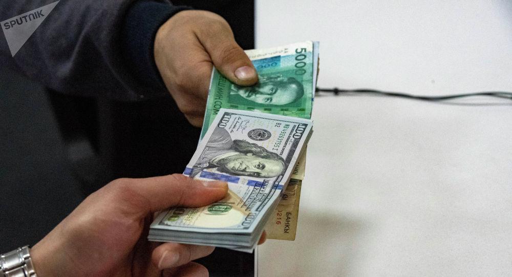 Пачка сто долларовых и пяти тысячных сомовых купюр на столе держат люди в руках. Иллюстративное фото