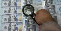 Мужчина с лупой рассматривает долларовые и сомовые купюры. Иллюстративное фото