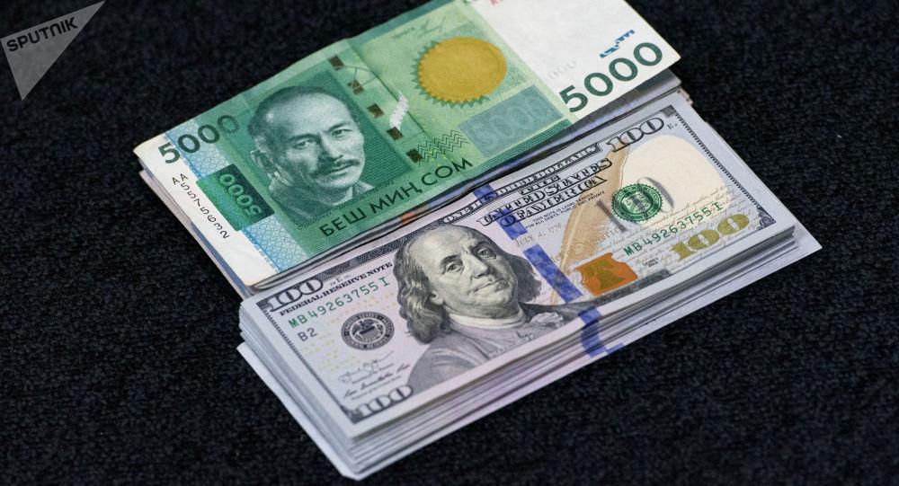 Пачка сто долларовых и пяти тысячных сомовых купюр. Иллюстративное фото