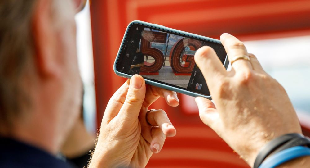Мужчина снимает на телефон логотип 5G. Архивное фото