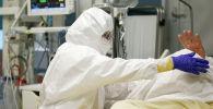 Медицинский работник осматривает пациента в отделении COVID-19. Архивное фото