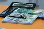 Сто долларовая и пяти тысячная сомовая купюра на калькуляторе. Иллюстративное фото