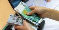 Долларовые и сомовые купюры в руках у женщины. Иллюстративное фото