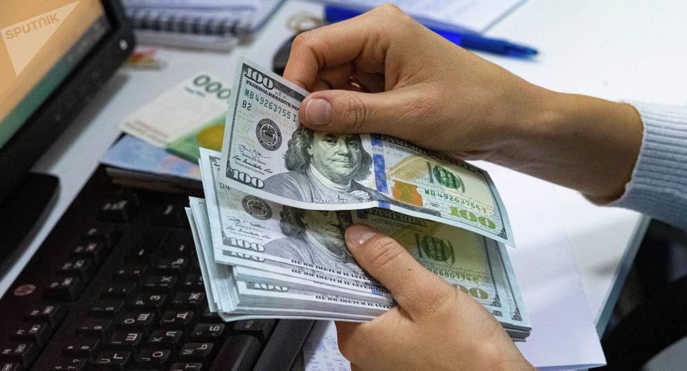Женщина держит долларовые купюры в руках. Иллюстративное фото