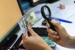 Женщина рассматривает через  лупу сто долларовую купюру. Иллюстративное фото