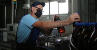Работник у конвейера пивной продукции. Архивное фото