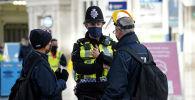 Сотрудник полиции беседует с людьми в главном вестибюле на вокзале Ватерлоо в Лондоне