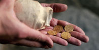 Археолог держит кувшин с золотыми монетами. Архивное фото