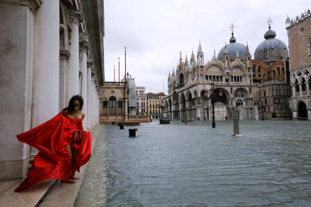 Италия, Венециянын Сан-Марко аянтын суу каптап, узун көйнөк кийген кыз анын четинен басып баратат