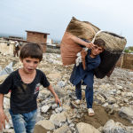 Афганистан, Парван провинциясын сел каптагандан кийин үйдө калган оокатын ташып бараткан балдар