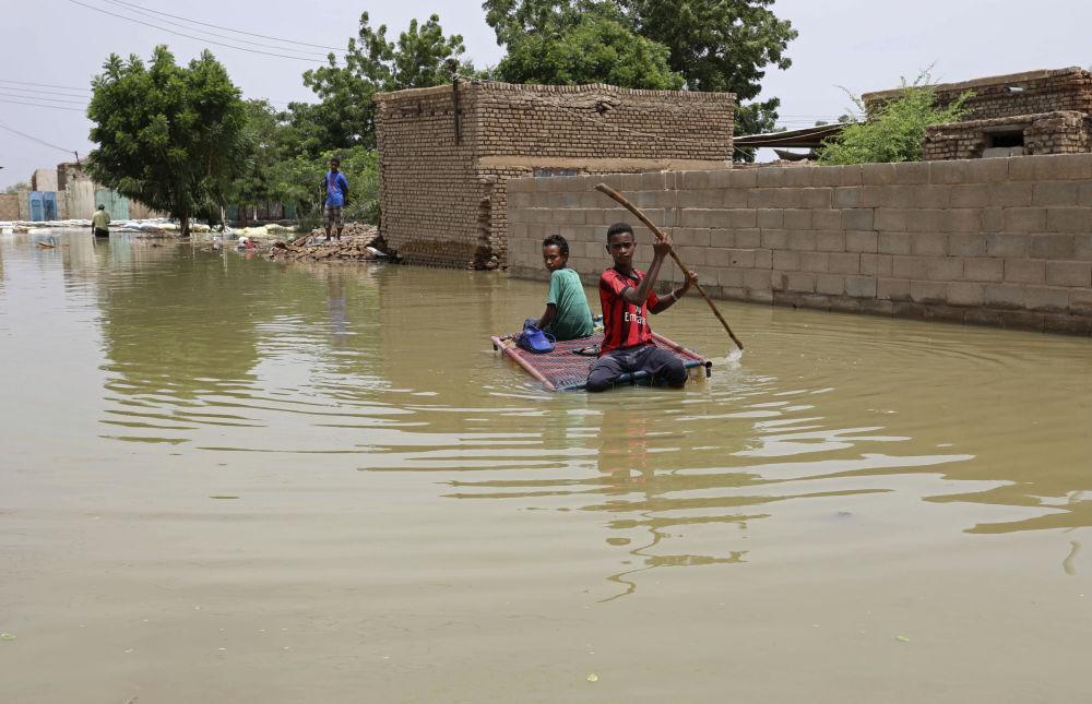 Судан, Салмания шаарындагы көчөлөрүн суу каптап, өздөрү жасап алган кайык менен бараткан балдар