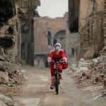Иракская женщина, одетая как Санта-Клаус, катается на велосипеде во время распространения коронавирусной болезни (COVID-19) в старом городе Мосул. Ирак, 18 декабря 2020 года