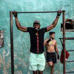 Мужчина подтягивается на фоне новой пандемии коронавируса в уличном спортзале в Гаване. Куба, 21 декабря 2020 года